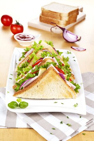 sandwich with bacon cheese vegetables toasted bread on the breakfast table .
