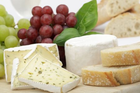 cheese with mould slices bread grapes on the board . Stock Photo