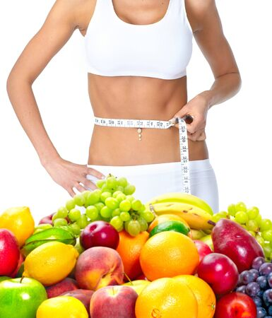 girl with a centimeter on the waist fruit vitamins white background .