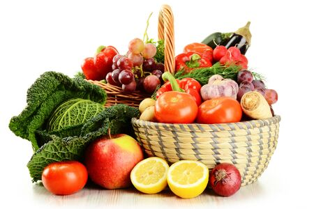 basket with vegetables and fruit on white background.