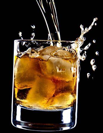 Whisky brandy ice spray on black background. Imagens