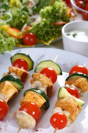 Barbecue on skewer of vegetables, tomatoes, mushrooms and courgette greens with dinner sauce.