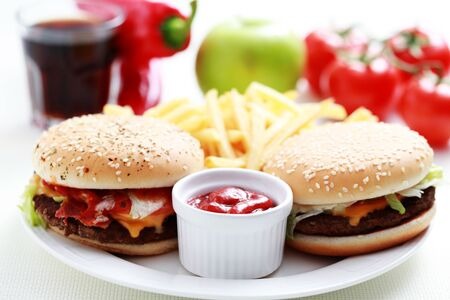 Hamburger with pepper, cherry, tomatoes with sesame seeds on white background.