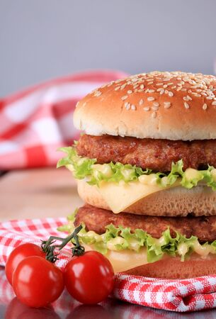 Hamburger cutlets cheese, tomato with sesame on wooden table. Imagens