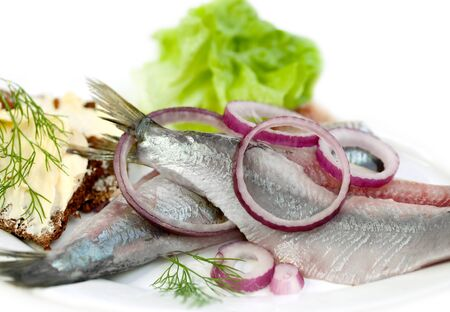 slices fish with lemon, onion, potato and greens on a white background.