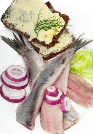 Fish herring fillet with onion, bread, butter and sandwiches on white background.
