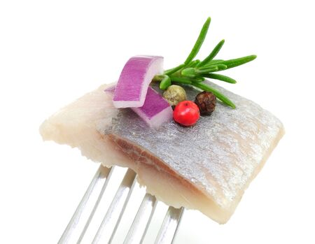 Herring fillet fish with onion spices and greens on white background.