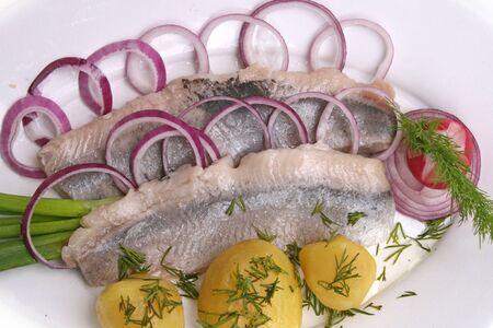 Herring fillet fish potatoes boiled onion greens on a white background. Imagens