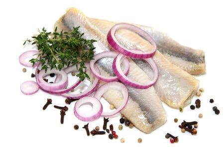 Herring fillet fish onion spices greens on white background.