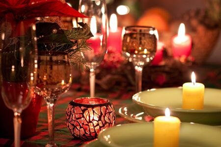 Christmas candle glasses on dinner table.