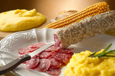 Sausage, mashed, corn on white dish with knife on brown background.