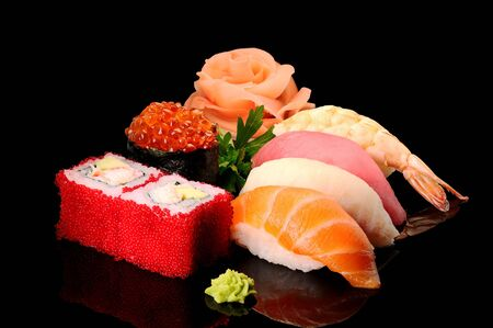Set of Rolls of Sushi Fish Rice Japanese Kitchen Curves Seafood on a Black Background . Imagens