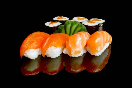 Rolls of sushi fish rice salmon seafood cucumber on a black background .