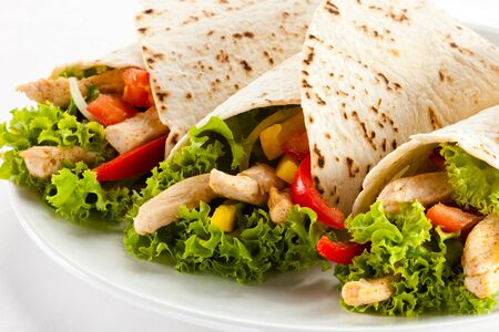 Shaurma pita bread chicken vegetable lettuce leaves on a white background . Imagens