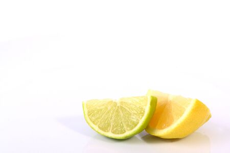 Lime lemon citrus fruit wedges on a white background . Imagens