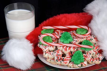 Christmas milk sweets candy cap Santa black background . Imagens - 131821067