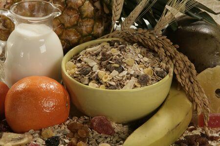 Meusli flakes, banana, orange, milk and pineapple raisins close up . Imagens