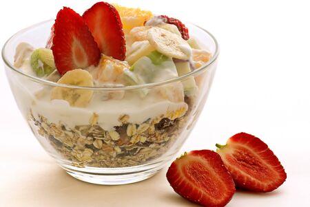 Meusli flakes berries fruit cream yogurt milk bananas strawberry white background .