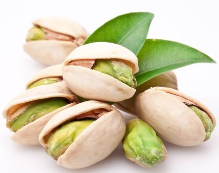 Pistachio nuts core leaves white background . Imagens