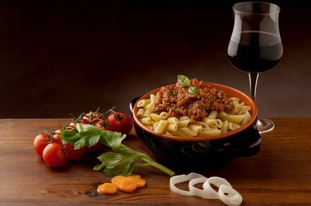 Pasta mince meat meal dinner dinner tomatoes greens glass wine table on dark background . Imagens - 131597962