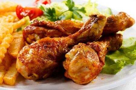 Mangiare la cena cena stinco di pollo patatine fritte su uno sfondo bianco. Archivio Fotografico