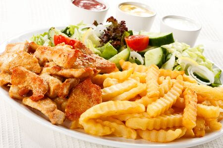 Lunch dinner meal fries chicken fillet vegetables greens white background sauces .