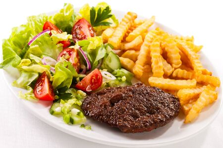 Eating dinner dinner fries fries chop beef vegetables greens cucumber tomatoes onion white background .