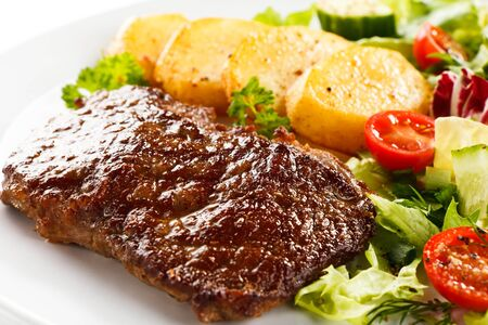 Meat fried potatoes greens vegetables tomatoes meal dinner dinner white background . Imagens - 131598168
