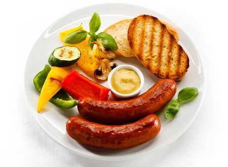 Lunch dinner dish meal sausage fried vegetables mustard mushrooms white background .