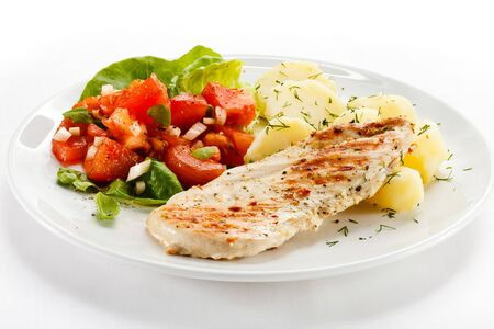 Fillet of chicken breast meal dinner dinner dish potato greens salad vegetables white background .