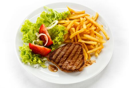 Meat fried French fries tomatoes tomatoes dinner dinner dinner kind of top white background . Imagens