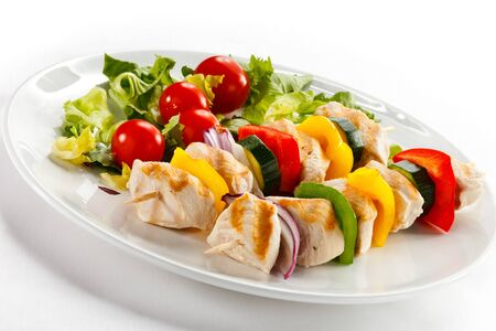 Barbecue skewer chicken vegetables onion tomatoes pepper white background .