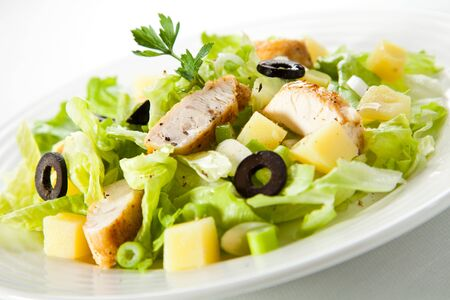 Vegetable salad greens pineapple olives chicken spice white background . Imagens