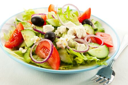 Greek tomato salad cucumbers onion vegetables olives cheese white background .