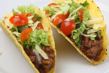 Mexican tacos stuffing minced vegetables tomato cheese greens white background .