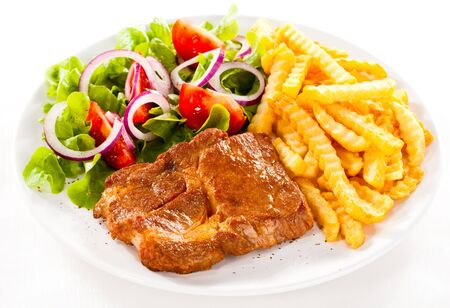 Eating dinner dinner fries chop pork vegetables greens tomatoes onion white background .