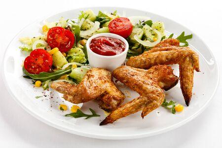Eating dinner dinner chicken wings vegetables corn tomatoes sauce white background .