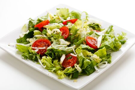 Vegetable salad greens tomatoes cucumber cabbage white background . Imagens - 131598184