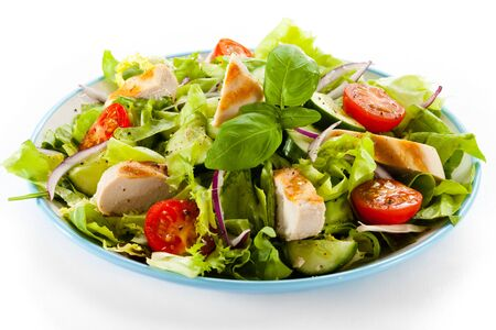 Vegetable salad greens chicken fillet cucumber tomato onion white background .
