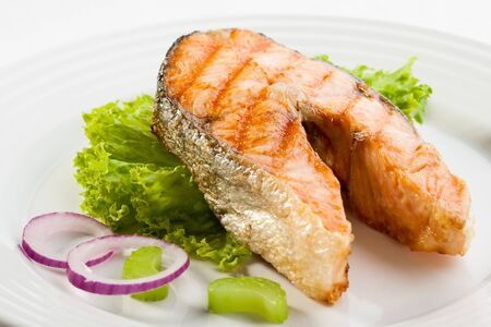 Fish roasted grilled salmon greens onion white background . Imagens