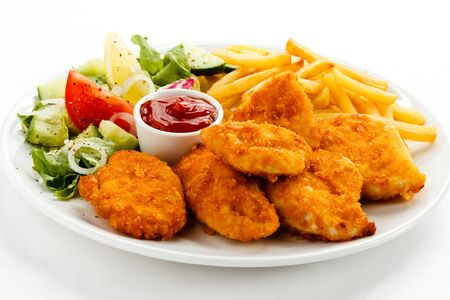 Nuggets chicken fillet sauce tomatoes fries white background .