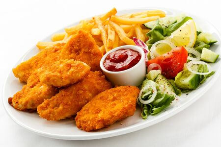 Nuggets chicken fillet sauce tomatoes fries white background . Stockfoto