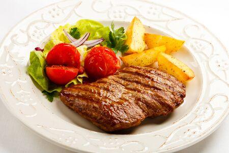 Carne a la parrilla patatas tomates verdes fondo blanco. Foto de archivo