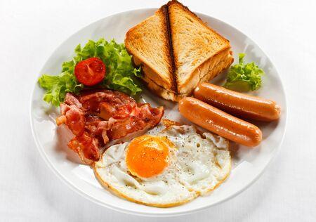 Jajecznica z kiełbaskami tosty śniadaniowe opiekane grzanki pomidorowe.