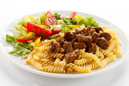 Pasta meat vegetables tomatoes pepper white background .