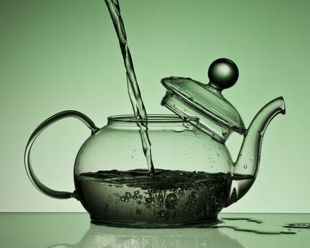 kettle pours water gray green color . Reklamní fotografie