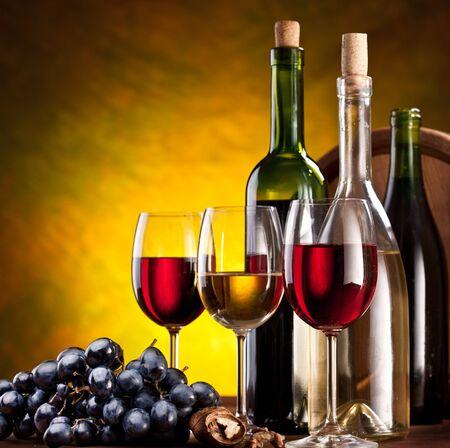 Vino uvas nueces botellas vasos barril fondo amarillo. Foto de archivo