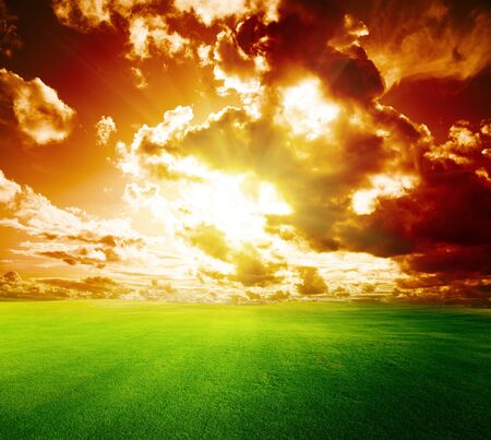 Meadow field grass sky sun behind clouds .