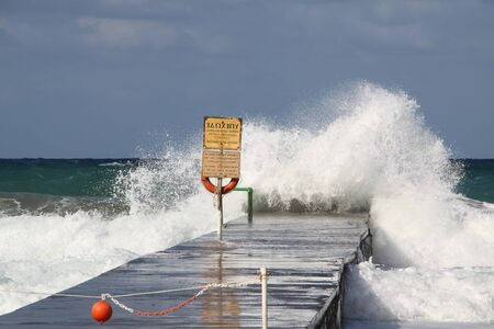 Wave splashes sea pier blue sky . Stockfoto
