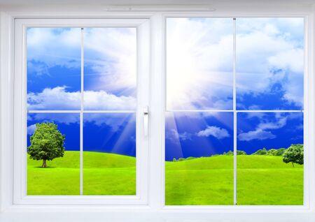 Window frame hills trees blue sky sun .